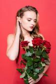 junge Frau blickt auf Rosen und fixiert rote Haare