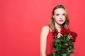 mladá žena drží růže a dívá se na kameru na červené
