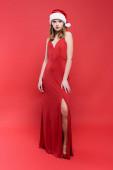 volle Länge der eleganten Frau in Kleid und Weihnachtsmütze steht auf rot