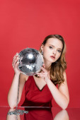 young woman holding shiny disco ball and looking at camera on red