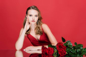 mladá žena při pohledu na kameru v blízkosti růží na červené