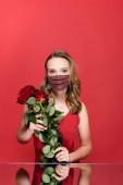 Frau in Schutzmaske mit Strass und Rosen auf Rot