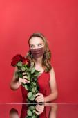 mladá žena v ochranné masce s kamínky držícími růže na červené