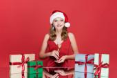 boldog nő télapó kalap kezében pohár pezsgő közelében rózsák és karácsonyi ajándékok piros