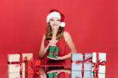 fiatal boldog nő télapó kalap mosolygós közel karácsonyi ajándékok piros