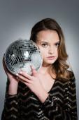 mladá žena dívá na kameru, zatímco drží disco míč na šedé