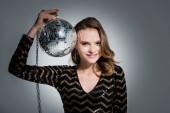 pozitív fiatal nő nézi kamera, miközben tartja disco labda szürke