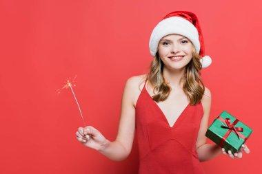 Noel Baba şapkalı neşeli kadın elinde Noel hediyesi kutusu ve kırmızıda maytap tutuyor.