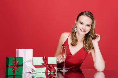 Young happy woman holding glass of champagne near christmas presents on red stock vector
