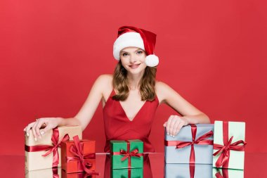 Happy woman in santa hat smiling near christmas presents on red stock vector