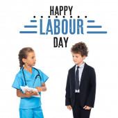 Kind im Arztkostüm hält digitales Tablet in der Nähe lockigen Jungen in formeller Kleidung und glücklichen Tag der Arbeit Schriftzug auf weiß