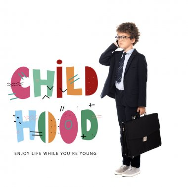 Curly boy in suit and glasses holding briefcase while talking on smartphone near childhood, enjoy life while you are young lettering on white stock vector