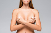 Cropped view of nude woman covering breast with hands isolated on grey