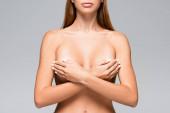 Ausgeschnittene Ansicht einer nackten Frau, die ihre Brust mit isolierten Händen auf Grau bedeckt