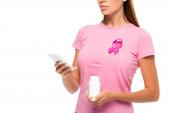 Ausgeschnittene Ansicht von Frau mit Brustkrebs Bewusstsein Band hält Glas mit Pillen und mit Smartphone isoliert auf weiß