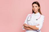 Junger Arzt in weißem Mantel und Stethoskop blickt isoliert auf rosa Kamera