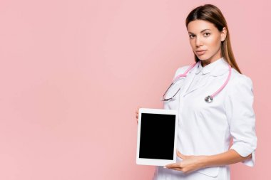 Doctor in white coat holding digital tablet with blank screen and looking at camera isolated on pink stock vector