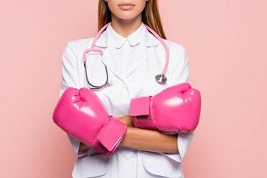 Cropped view of doctor in white coat and pink boxing gloves standing with crossed arms isolated on pink stock vector