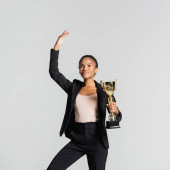 smiling african american businesswoman performing ballet with golden cup isolated on grey