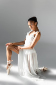 graceful african american ballerina in dress on white background