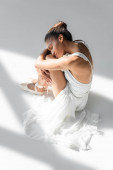 graceful african american ballerina in dress sitting on floor on white background