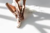 cropped view of graceful african american ballerina in pointe shoes sitting on floor on white background