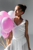 půvabná africká americká baletka v šatech s balónky na bílém pozadí