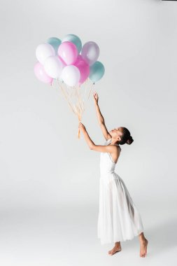 Barefoot graceful african american ballerina in dress with balloons on white background stock vector