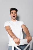 šťastný mladý muž v bílém tričku na židli izolované na šedé