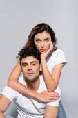 fiatal pár fehér pólóban átöleli elszigetelt szürke