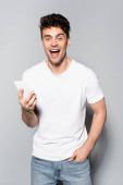 boldog fiatal férfi fehér pólóban okostelefonnal elszigetelt szürke