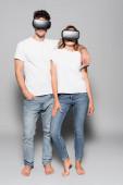 alkalmi fiatal pár fehér pólóban és vr headset elszigetelt szürke