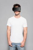 alkalmi fiatal férfi fehér pólóban és vr headset elszigetelt szürke
