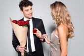 elegant young man with bouquet doing marriage proposal isolated on grey
