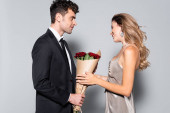 elegáns fiatal férfi ajándék csokor a nő elszigetelt szürke
