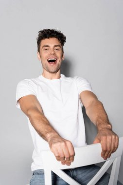 Happy young man in white t-shirt on chair isolated on grey stock vector