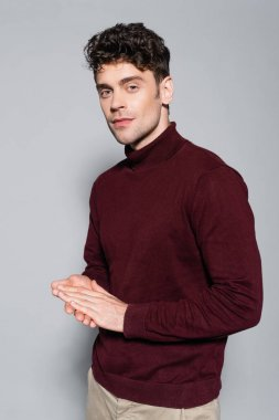 Young man in burgundy jumper posing isolated on grey stock vector
