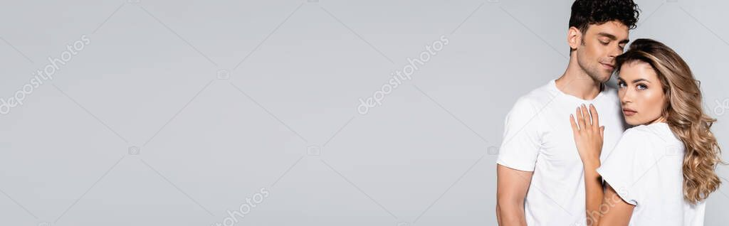 Young couple in white t-shirts posing isolated on grey, banner stock vector