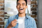 ámulatba ejtett afro-amerikai férfi nevet, miközben kezében csésze kávét