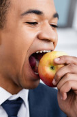african american businessman biting apple