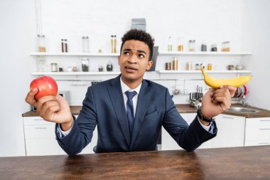 Puzzled african american businessman choosing between apple and banana stock vector