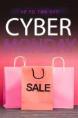 Einkaufstasche mit bis zu 70 Prozent Rabatt in der Nähe von Papiertüten, Cyber-Monday-Schriftzug auf rosa, Black-Friday-Konzept