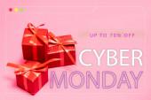 rote Geschenkboxen mit bis zu 70 Prozent Rabatt, Cyber-Monday-Schriftzug auf rosa unscharfem Hintergrund