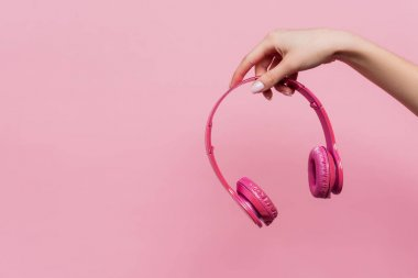partial view of woman holding wireless headphones in hand isolated on pink