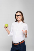 smiling young pregnant businesswoman in glasses with glass of water and apple isolated on grey
