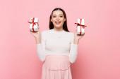 glückliche junge hübsche schwangere Frau mit Geschenken isoliert auf rosa