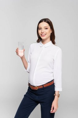 Smiling young pregnant businesswoman with glass of water isolated on grey stock vector