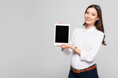 smiling young pregnant businesswoman presenting digital tablet isolated on grey