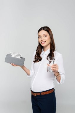 Smiling young pregnant businesswoman with napkins and water isolated on grey stock vector