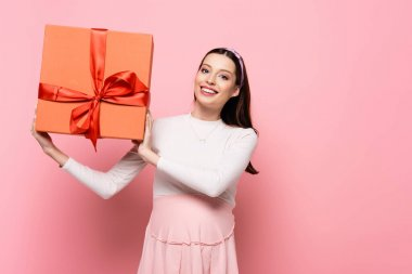 Happy young pretty pregnant woman with gift isolated on pink stock vector
